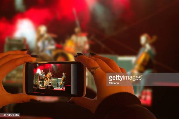woman photographing live concert - photo messaging stock pictures, royalty-free photos & images