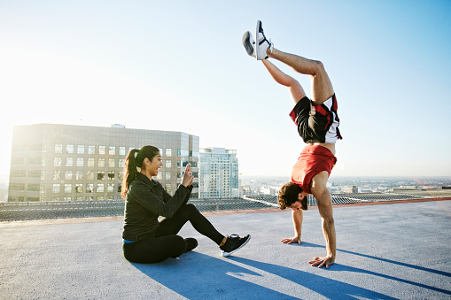 Woman photographing man doing handstand on urban rooftop - gettyimageskorea