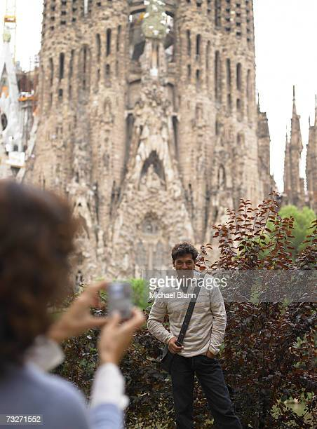 woman photographing man in front of sagrada familia cathedral, barcelona, spain - familia stock-fotos und bilder