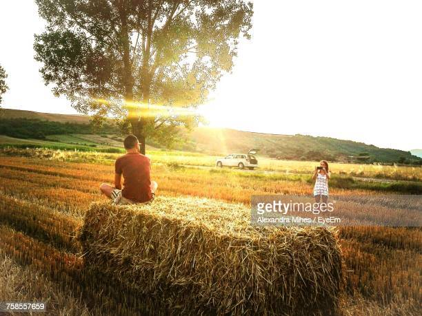 Woman Photographing Man Sitting On Hay Stack At Field Against Sky During Sunset