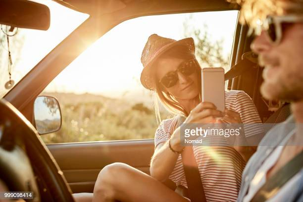 woman photographing man using mobile phone in car - independence stock pictures, royalty-free photos & images