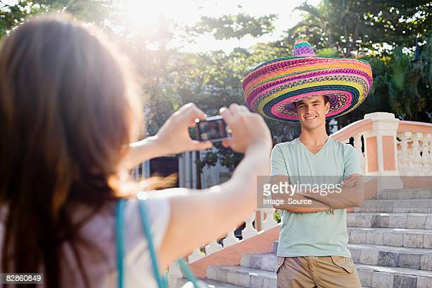 woman photographing man wearing sombreros - mexican hat stock pictures, royalty-free photos & images