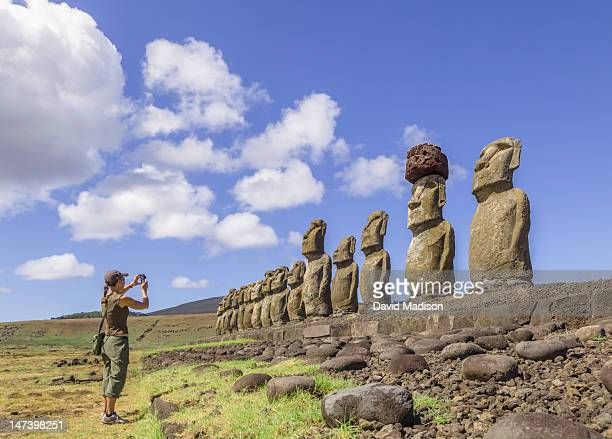 Woman photographing Moai statues.
