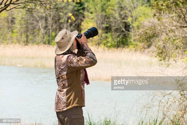 Woman photographing nature and bird, nature photographer