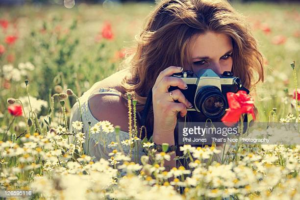 Woman photographing poppies in field