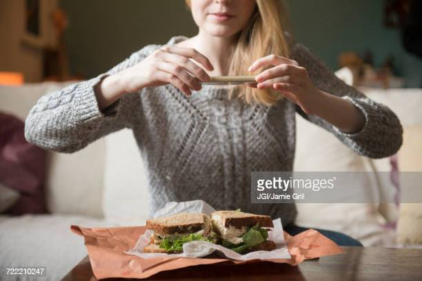 Woman photographing sandwich with cell phone