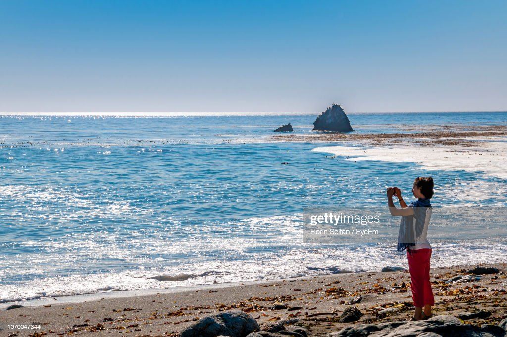 Woman Photographing Sea Against Clear Sky : Stock Photo