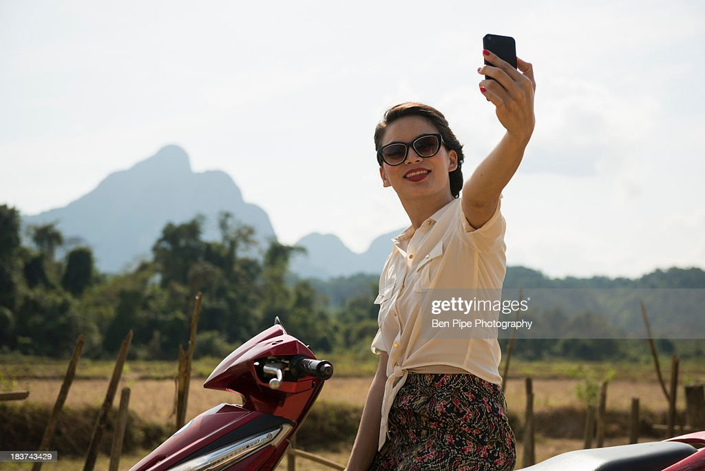 Woman photographing self on moped, Vang Vieng, Laos : Stock Photo
