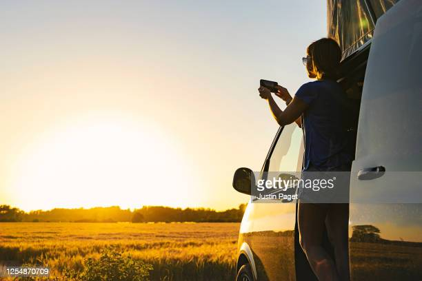 woman photographing sunset from her campervan - camper van stock pictures, royalty-free photos & images
