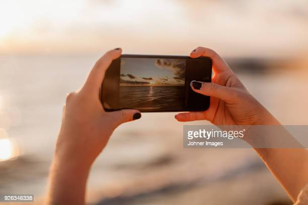 woman photographing sunset with smartphone - fotohandy stock-fotos und bilder