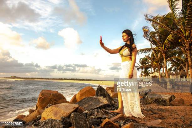 woman photographing the beach with mobile phone - natal brazil stock pictures, royalty-free photos & images