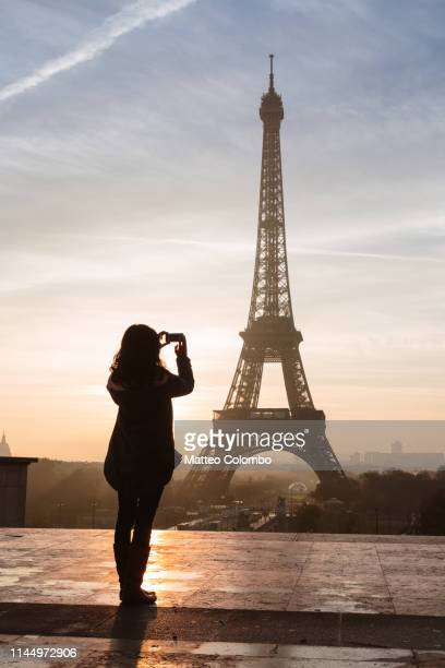 woman photographing the eiffel tower at sunset, paris, france - esplanade du trocadero stock pictures, royalty-free photos & images