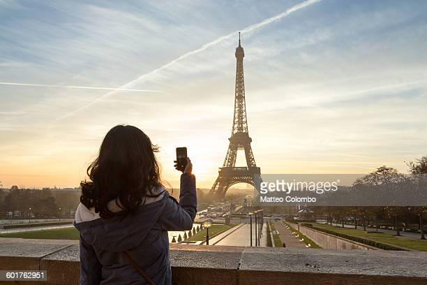 woman photographing the eiffel tower, paris - rear view photos stock photos and pictures