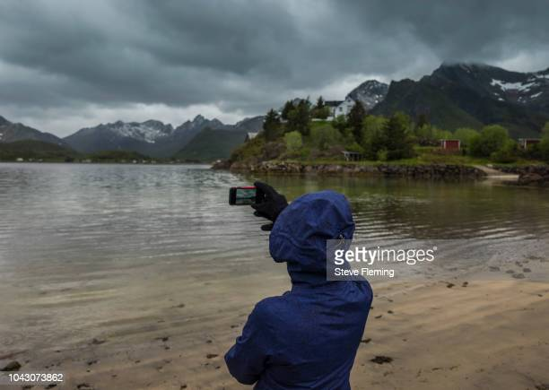 A woman photographing the landscape at Kabelvag, Lofoten Islands, Norway.