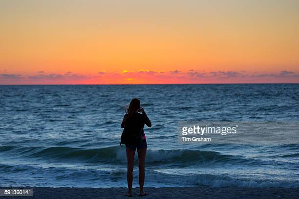 Woman photographing the sunset on Captiva Island in Florida USA