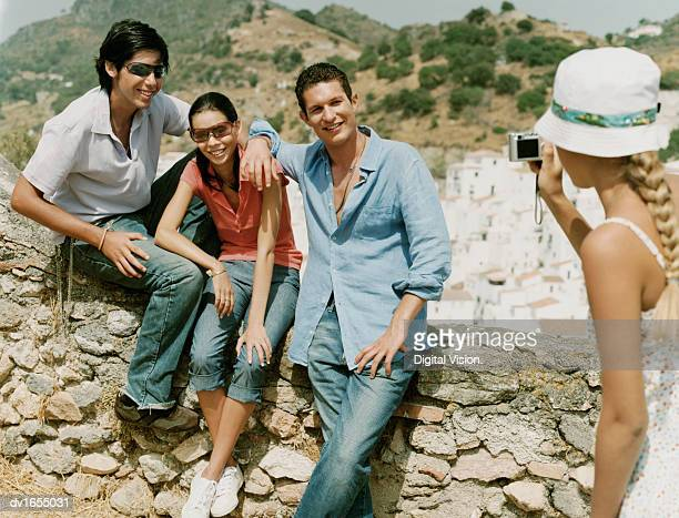 Woman Photographing Three Friends Sat on a Stone Wall with a Town in the Background