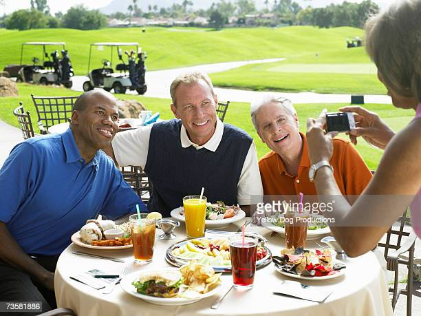 Woman photographing three men eating lunch at golf course