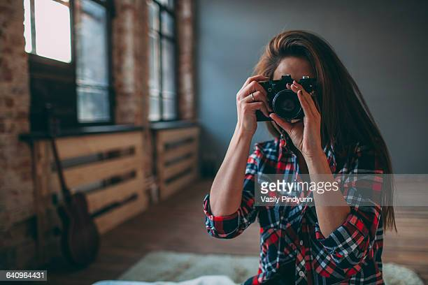 Woman photographing through SLR camera in bedroom at home