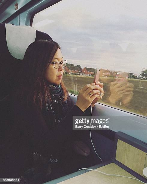woman photographing using smart phone in train - taken on mobile device stock photos and pictures