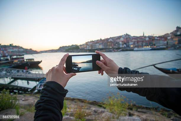Woman photographing view at dusk