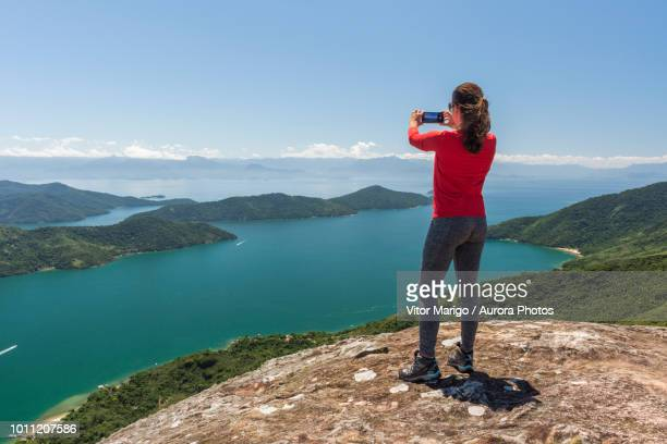 woman photographing view of sea from mountain, saco do mamangua, paraty, costa verde, brazil - capturing an image stock pictures, royalty-free photos & images