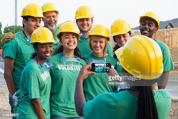 Woman photographing volunteers with cell phone