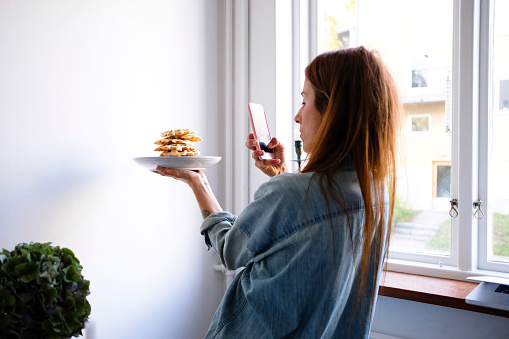 Woman photographing waffles through smart phone in plate by wall at home - gettyimageskorea