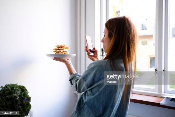 woman photographing waffles through smart phone in plate by wall at home - photographing stock pictures, royalty-free photos & images