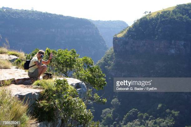 Woman Photographing While Crouching On Cliff Against Mountain