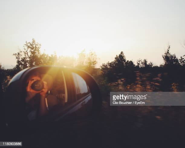 woman photographing while sitting in car during sunset - san miniato stock pictures, royalty-free photos & images