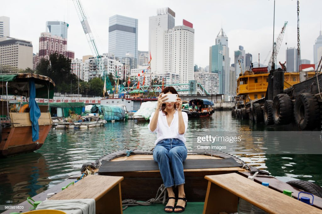 Woman photographing while sitting on boat in city : Stock Photo