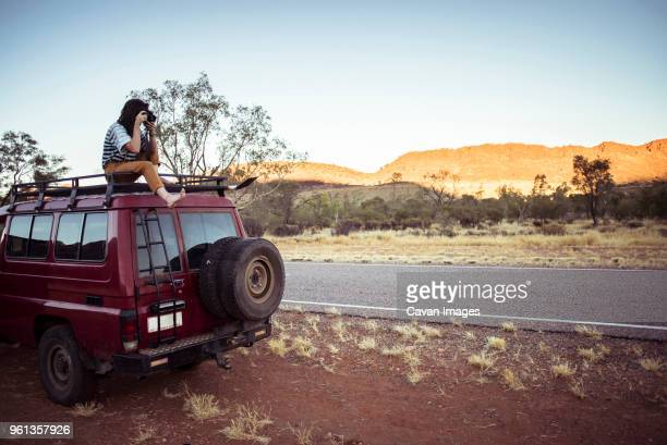 woman photographing while sitting on car roof at desert - alice springs stock pictures, royalty-free photos & images