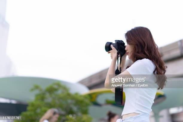 woman photographing while standing against sky - anuwat somhan stock photos and pictures