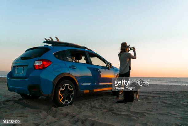 woman photographing while standing with dog by car at beach - car stock pictures, royalty-free photos & images
