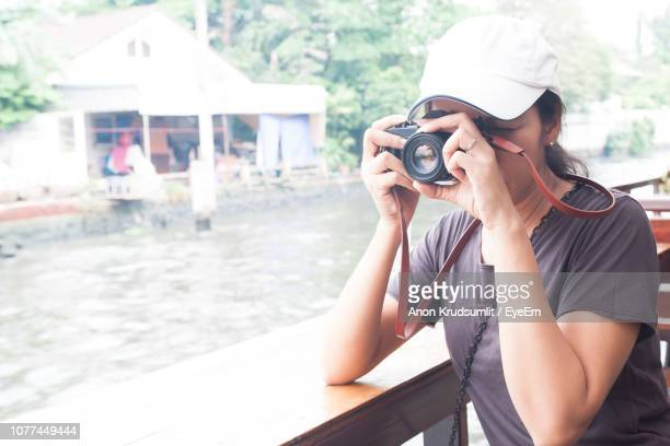 Woman Photographing With Camera By Canal