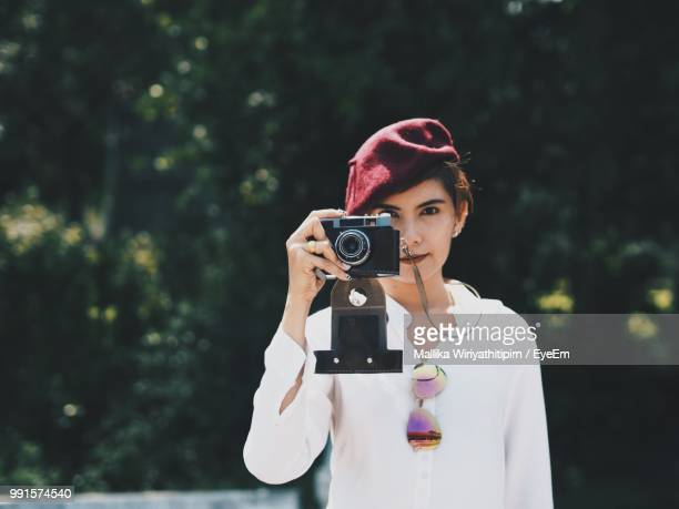 Woman Photographing With Camera Standing Against Trees