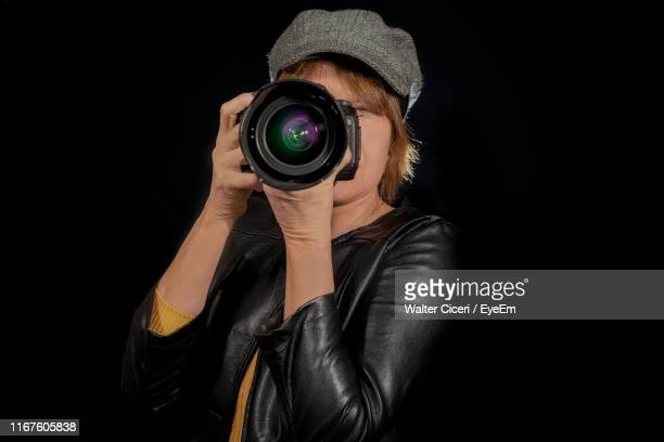 woman photographing with digital camera against black background - walter ciceri foto e immagini stock