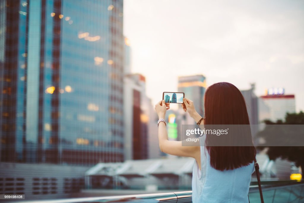 Woman photographing with smartphone in Central Business District of Hong Kong : Stock-Foto