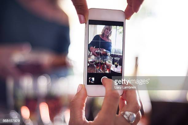 Woman photographing woman with champaign glasses