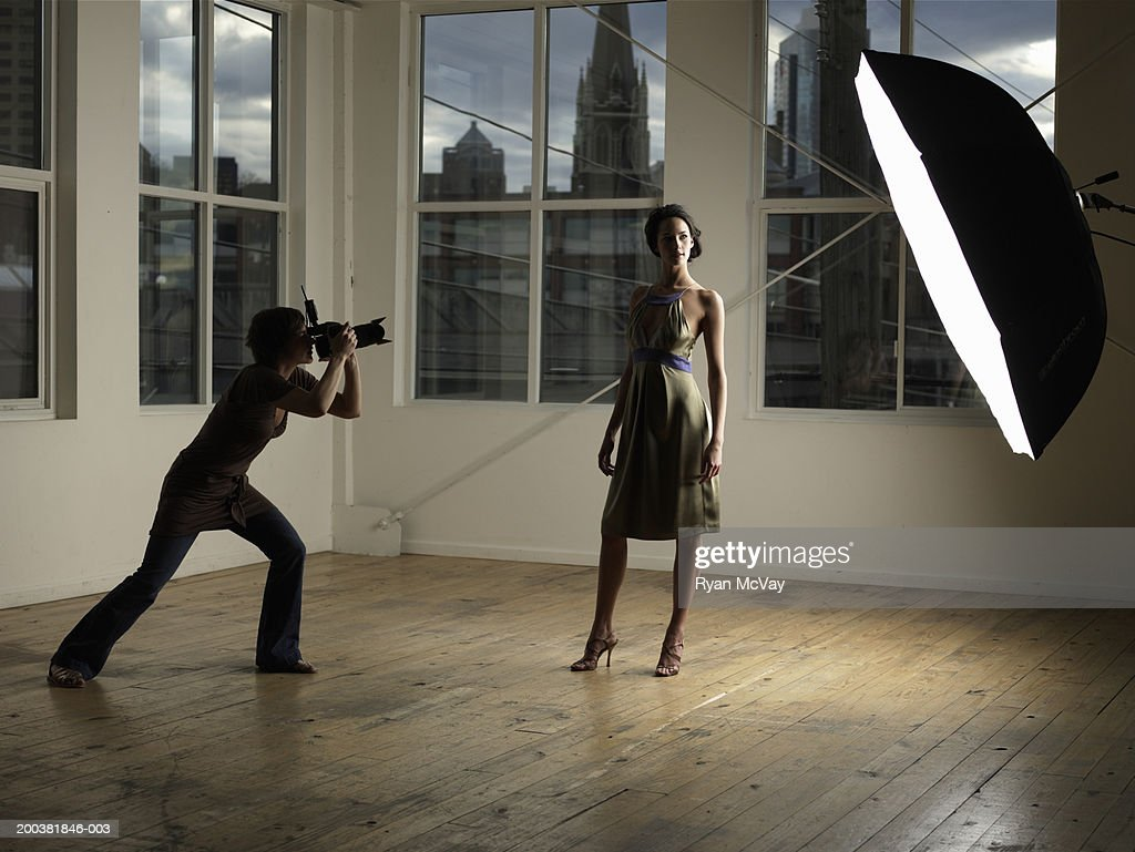Woman photographing young female model in photo studio, dusk : Stock Photo