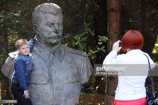 A woman photographs a boy next to the statue of Josef Stalin in Grutas Park April 30 2011 Every year on the Saturday which falls before May 1st...