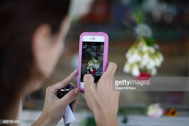 A woman photographs a bullet hole filled with flowers in the window of the IV Deli May 25 2014 in Isla Vista California According to reports 22 year...