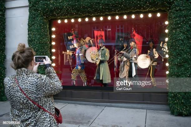 A woman photographs a Christmas window display at Selfridges on October 19 2017 in London England Selfridges is the first department store in the...