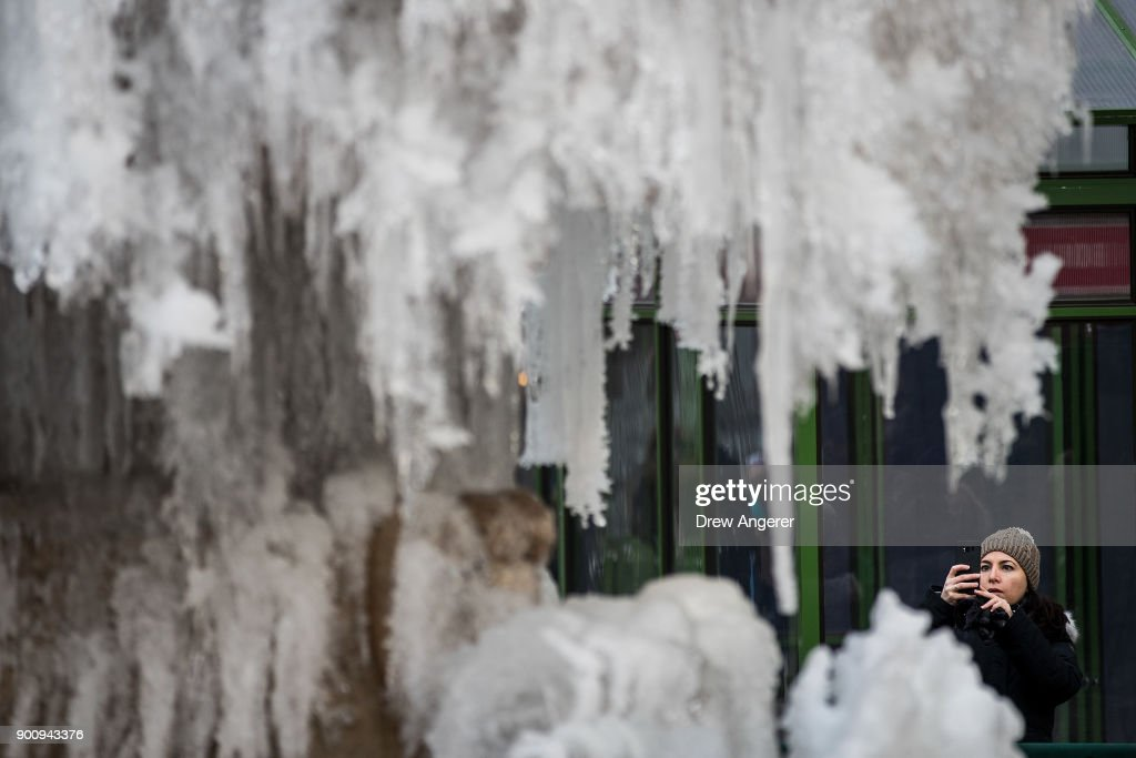 A woman photographs a frozen fountain in Bryant Park, January 3, 2018 in New York City. New York City was placed under a winter storm watch Wednesday as a major weather system is expected to threaten the area with heavy snow and powerful wind Wednesday night into Thursday.