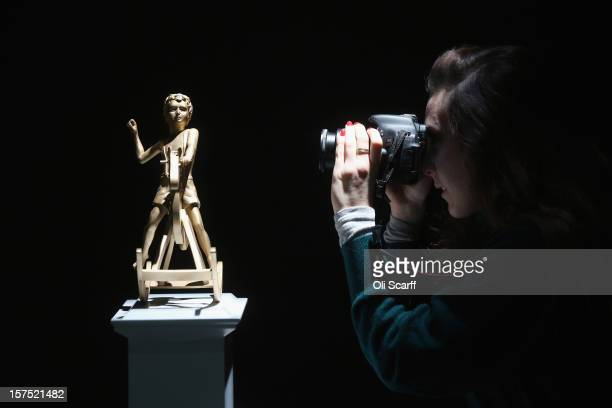 A woman photographs a maquette for the Fourth Plinth proposal by Elmgreen and Dragset entitled 'Powerless Structures Fig 101' which features in the...