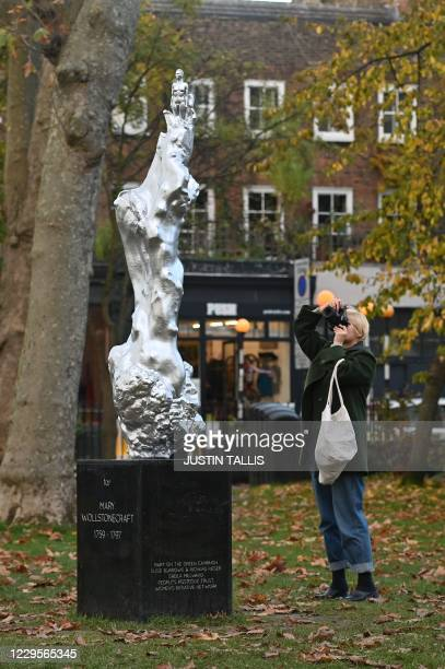 Woman photographs a new sculpture honouring 18th century British author and feminist icon Mary Wollstonecraft by British artist Maggi Hambling after...