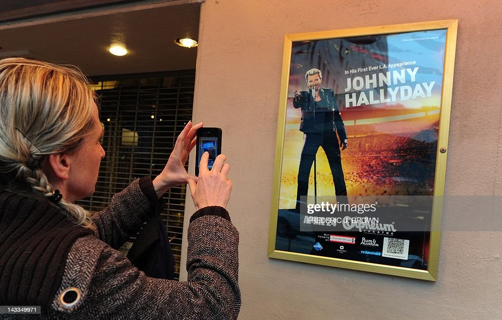 A woman photographs a poster as fans of veteran French rocker Johnny Hallyday await entry into the Orpheum Theater for his first concert in two years on April 24, 2012 in Los Angeles, California, where Hallyday begins a comeback tour two years after a health scare which nearly killed him in his adopted home of Los Angeles. In a tribute to the city 'where they saved my life,' the 68-year-old will start the more than 50-show tour aiming to 'make the public tremble with emotion,' he told AFP earlier this month. AFP PHOTO/Frederic J. BROWN
