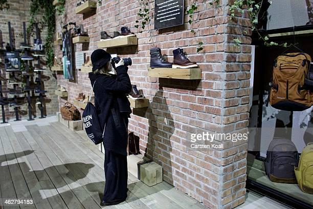 A woman photographs a presented shoe at the Timberland brand stand at the Bread and Butter trade show at the former Tempelhof airport during...
