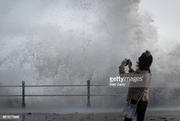 A woman photographs a wave whipped up by Hurricane Ophelia as it crashes over the seafront in Penzance on October 16 2017 in Cornwall England...