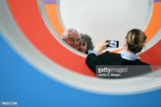 A woman photographs artist Daniel Buren and a woman with his work 'Like Child's Play ' at Carriageworks on July 6 2018 in Sydney Australia It is...